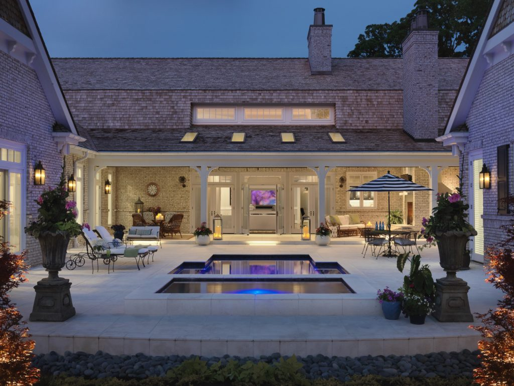 Well lit porch with patio furniture and a reflecting pool